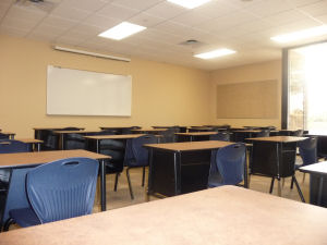 a low angle view of a classroom of desks with blank bulletin board and white board on the walls