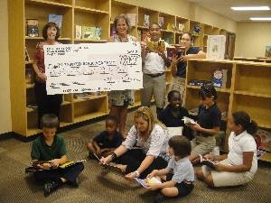 Charter school Administrators and children in school library with big donation check