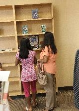 Mom and daughter check out new library shelving at charter school opening