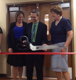 Board Members and CEO hold oversized scissors near ribbon just before cutting