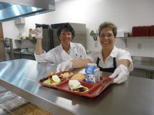 Chef and Assistant serve healthy school lunch