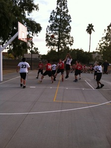 Boys in red and white shirts battling for a basketball shot at charter school game