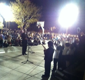 Bright light behind music director leading outdoor concert at traditional charter school
