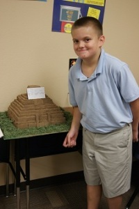 traditional charter school student displays model of dwelling
