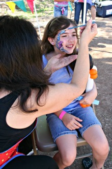 Young girl having her face painted at charter school event