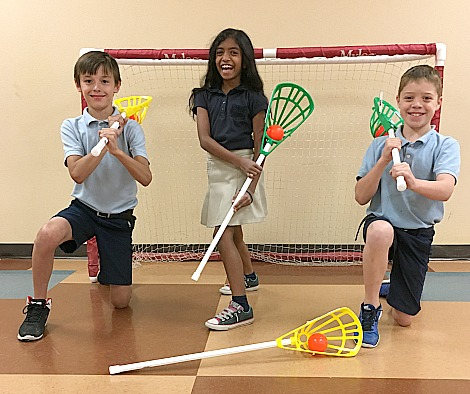 three middle school students with lacrosse equipment