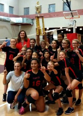 middle school girls pose with volleyball championship trophy