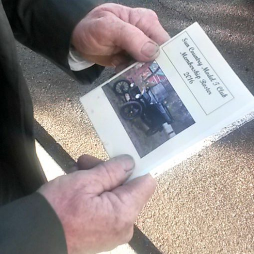 Gnarled hands holding brochure from Model T Club