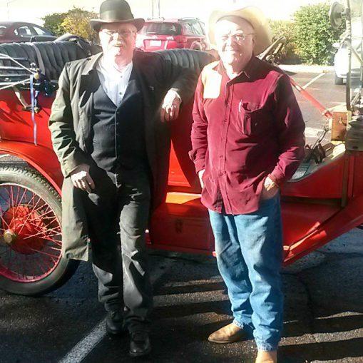 Two older gentlemen in vintage clothing with Model T car